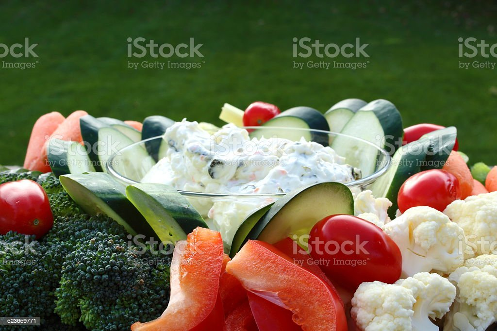 Closeup of a plate of raw vegetables and dip outdoorsCloseup of a plate of raw vegetables and dip outdoors stock photo