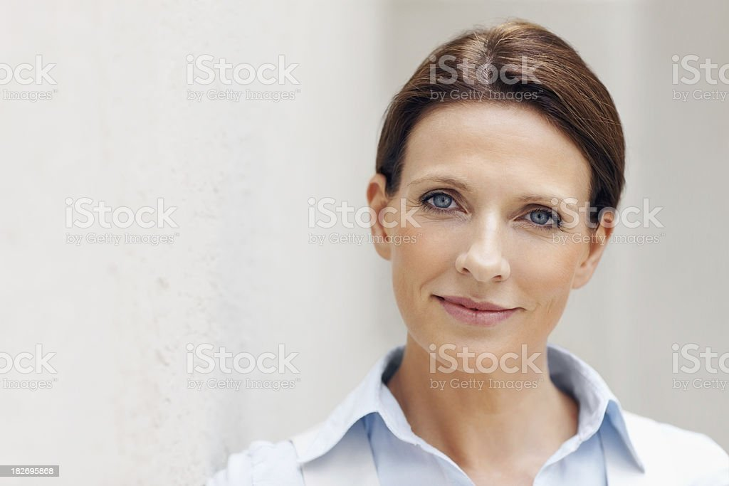 Closeup of a pretty woman leaning against the wall stock photo