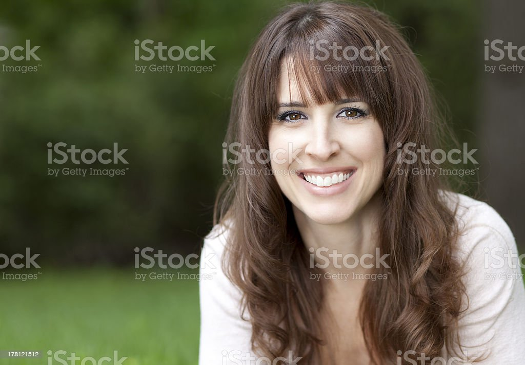 Close-up of a pretty woman on the grass smiling stock photo