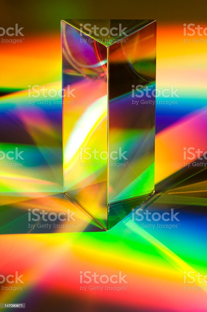 A closeup of a prism with rainbows reflecting off of it stock photo