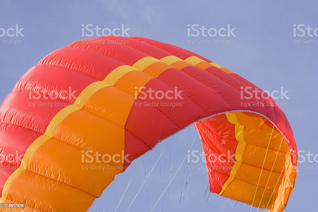 Close-up of a red and orange power kite against blue sky stock photo