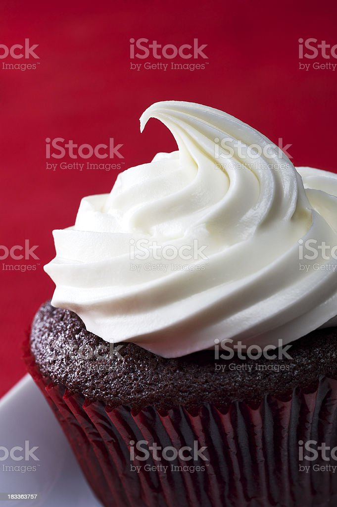 Close-up of a red velvet cupcake against a red background royalty-free stock photo