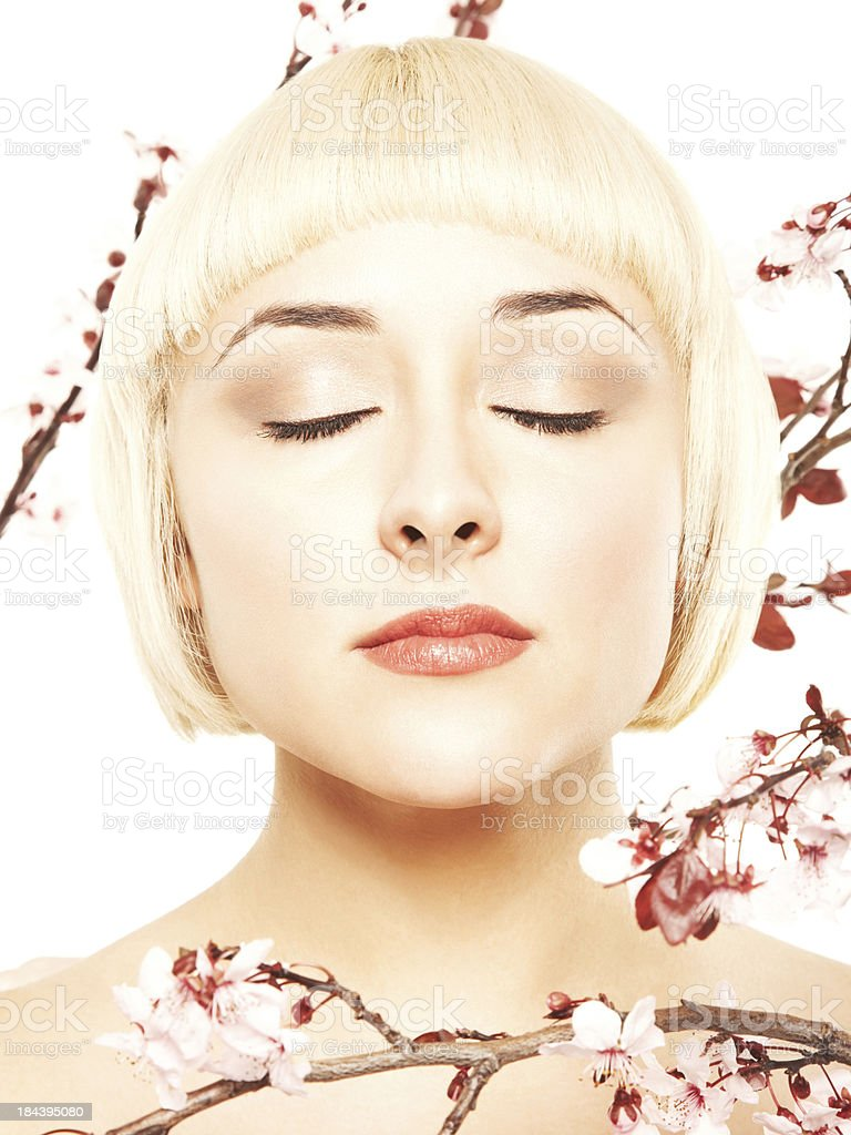 Close-up of a relaxed blonde with pink flowers around her royalty-free stock photo