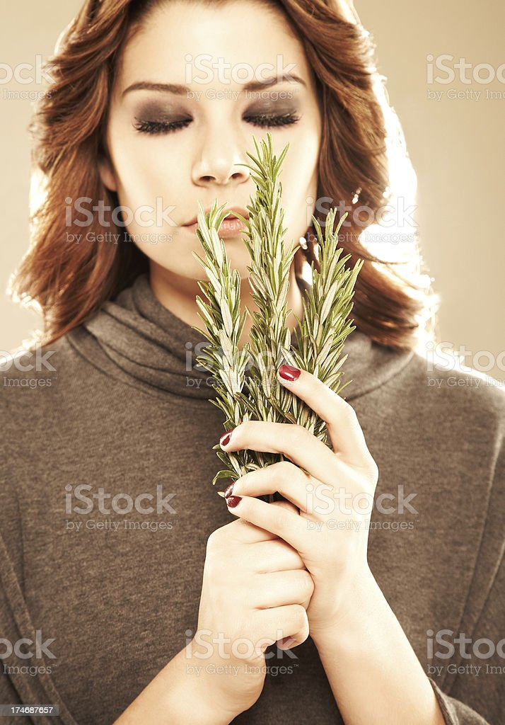 Close-up of a relaxed woman with rosemary leaves royalty-free stock photo