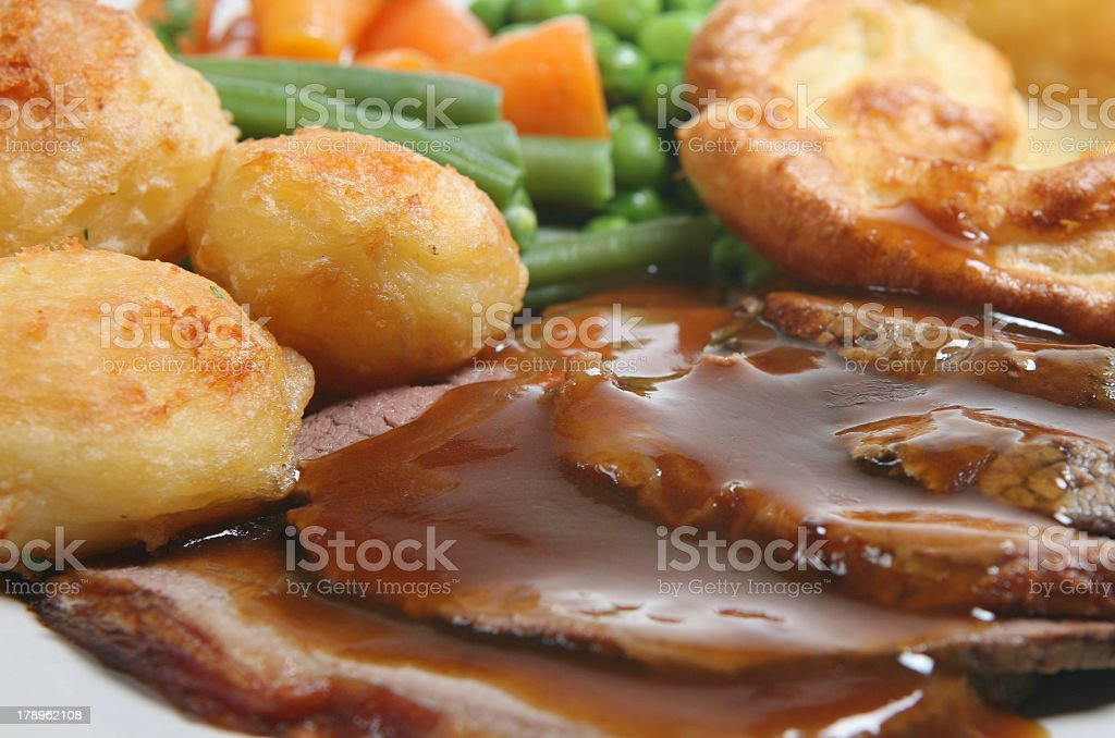 Close-up of a roast beef dinner with gravy and sides royalty-free stock photo