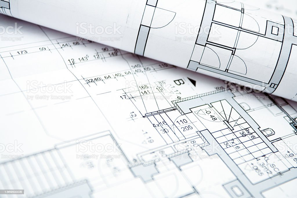 Close-up of a rolled house blueprint on top of unrolled one royalty-free stock photo