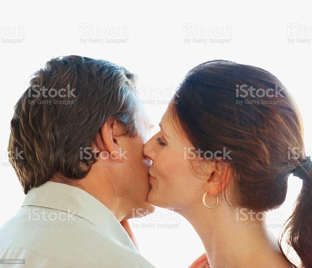 Closeup of a romantic woman kissing a man on the cheek stock photo