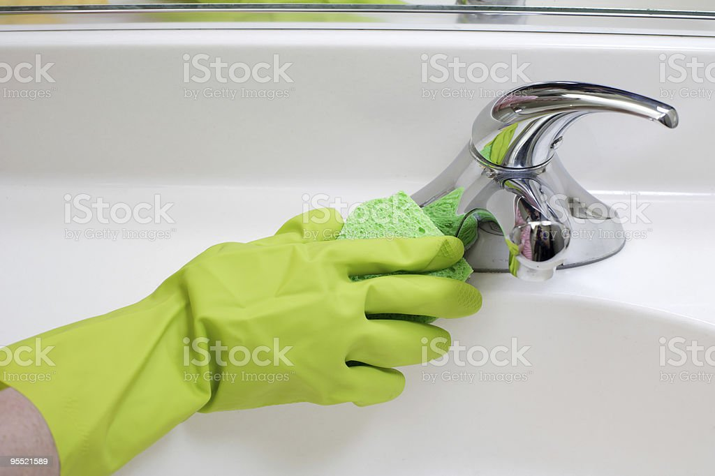Close-up of a rubber-gloved hand cleaning faucet royalty-free stock photo
