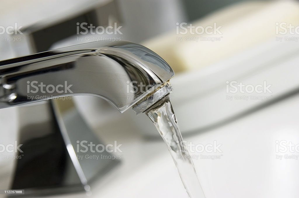 Close-up of a running silver bathroom faucet stock photo