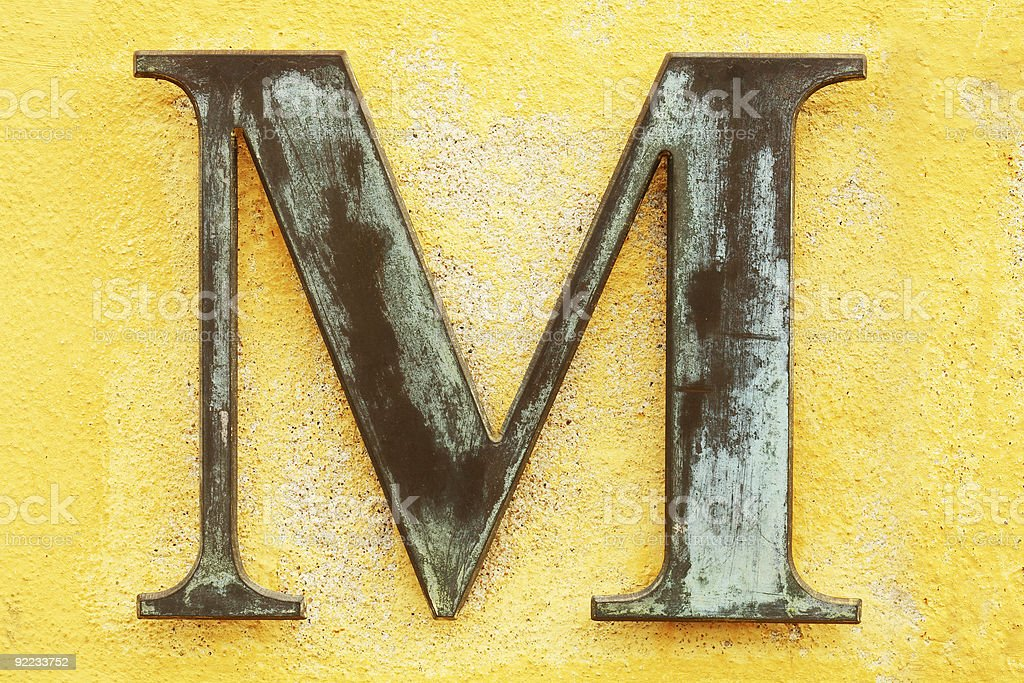 Close-up of a rustic dingy letter M on a yellow background  stock photo