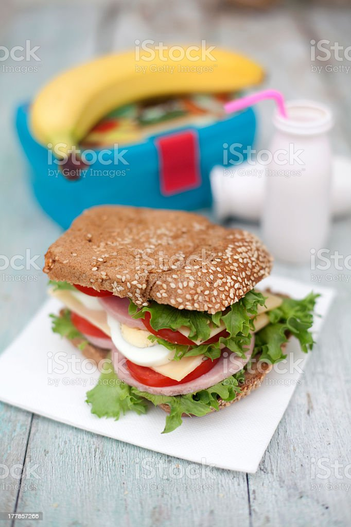 Close-up of a sand which with drinks next to lunchbox royalty-free stock photo