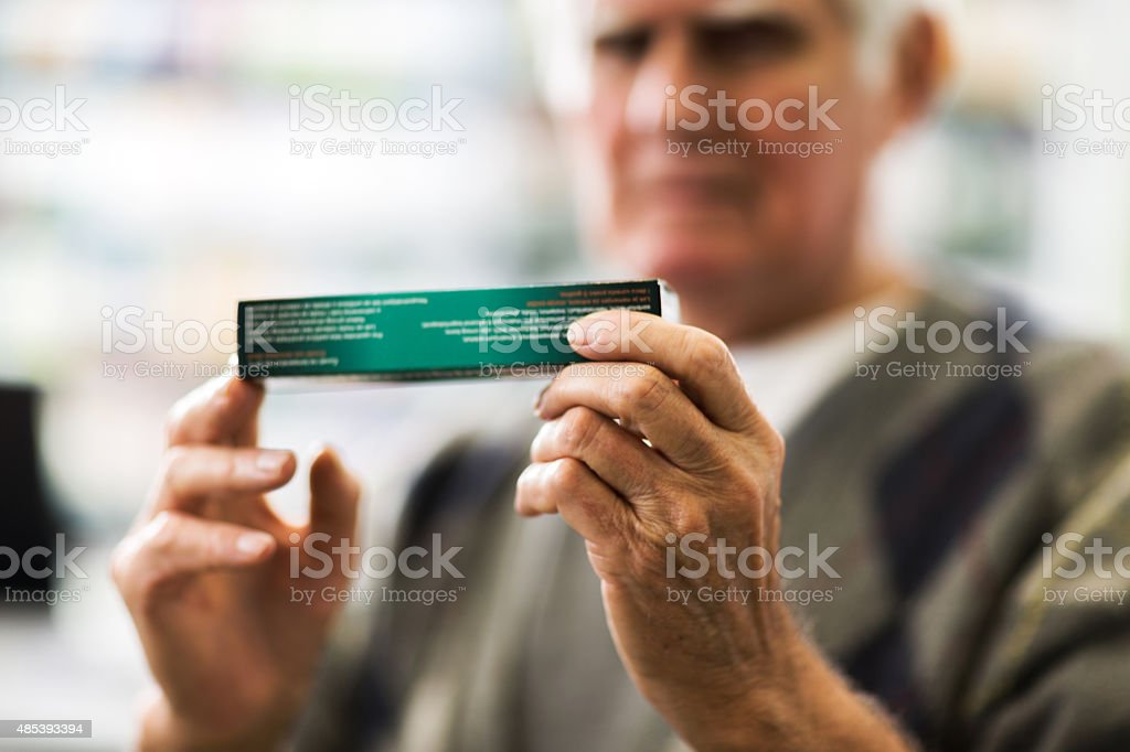 Close-up of a senior man holding medicine. stock photo