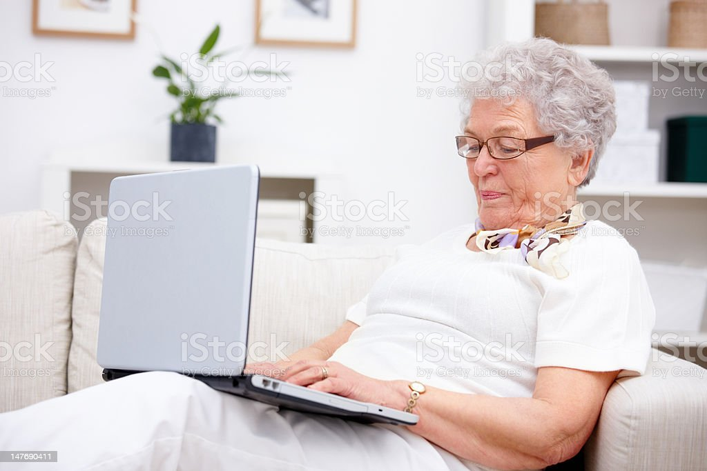 Close-up of a senior woman using laptop at home royalty-free stock photo