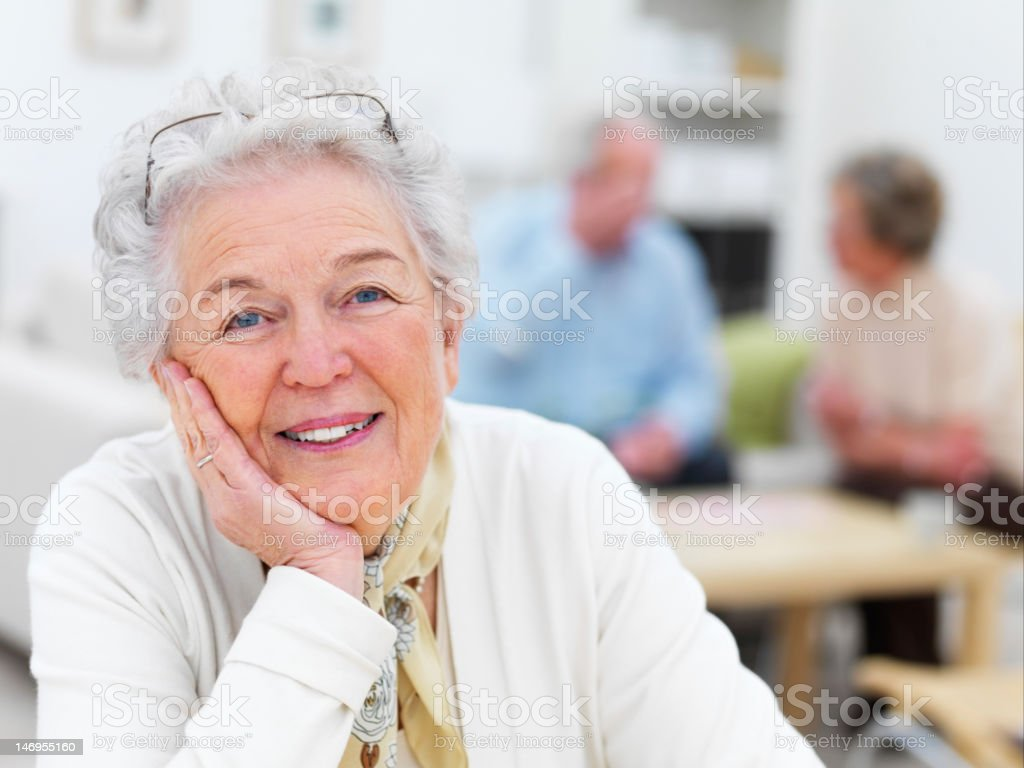Close-up of a senior woman with friends in background stock photo
