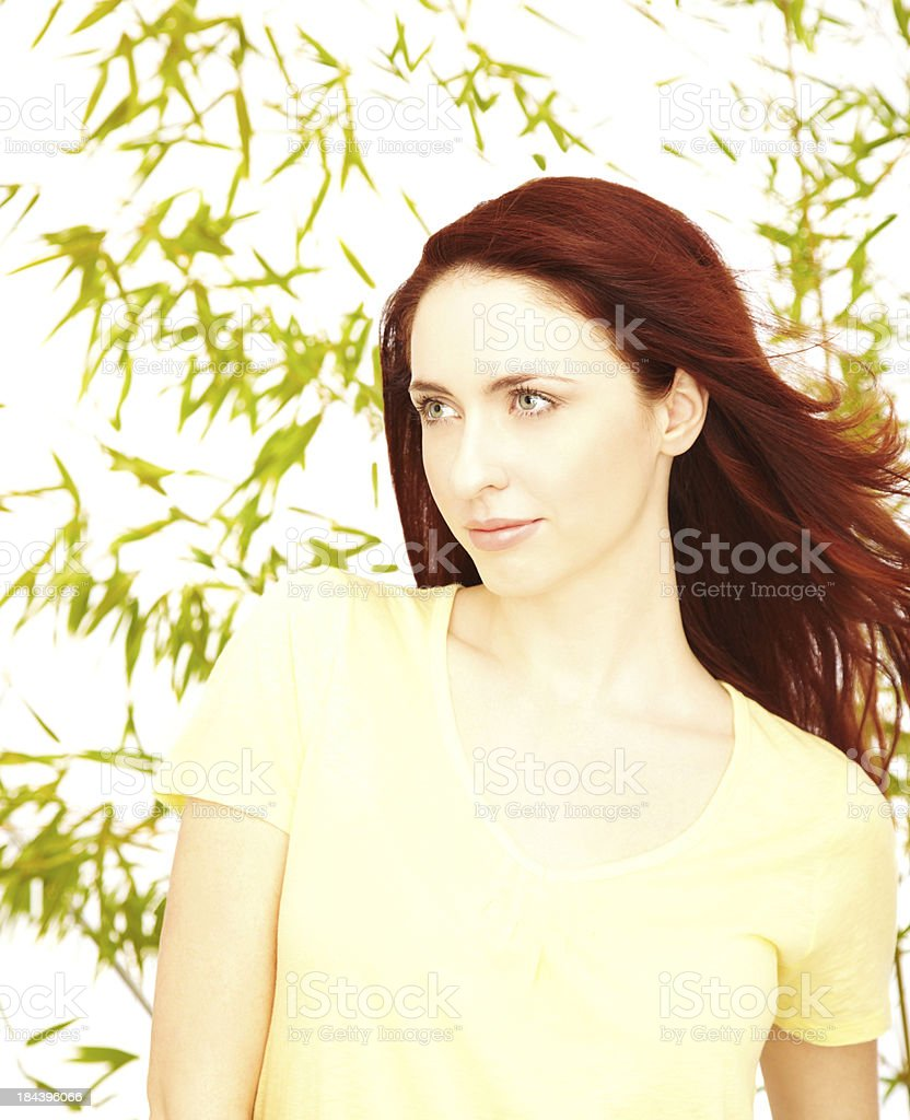 Close-up of a sensuous female with leaves in the background stock photo
