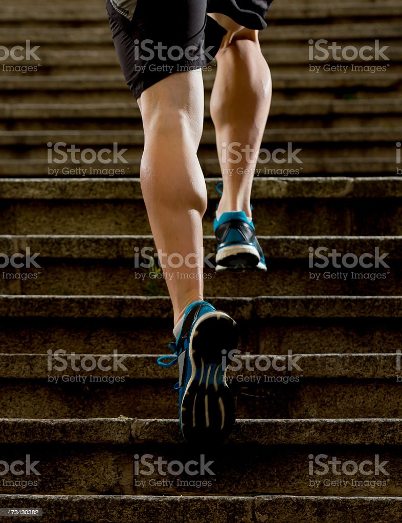 A close-up of a set of runners legs going up stairs stock photo