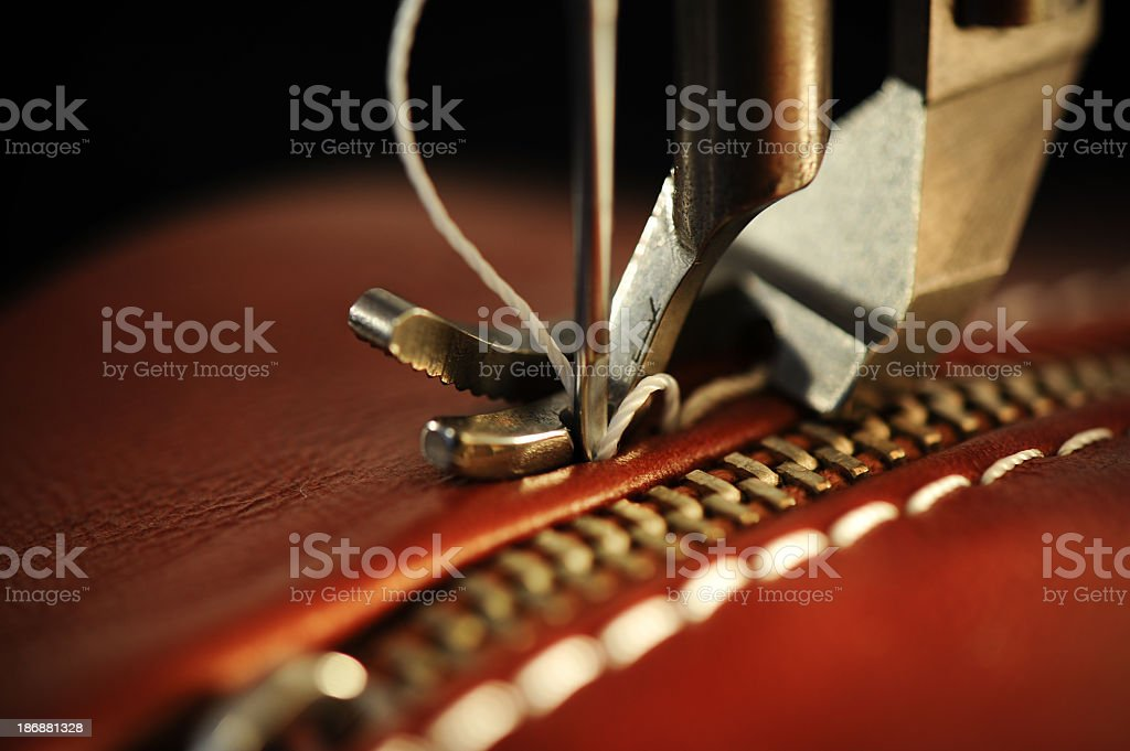 Close-up of a sewing machine with needle on red leather stock photo
