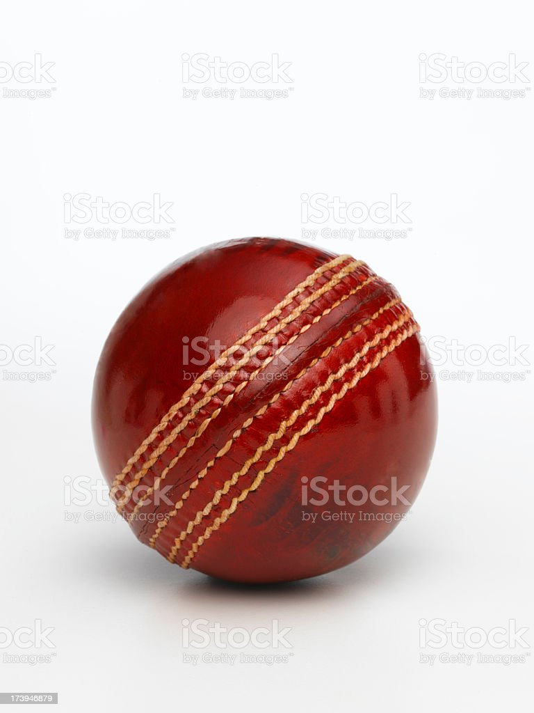 A closeup of a shiny red cricket ball on a white background stock photo