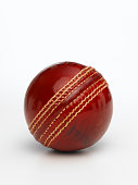 A closeup of a shiny red cricket ball on a white background