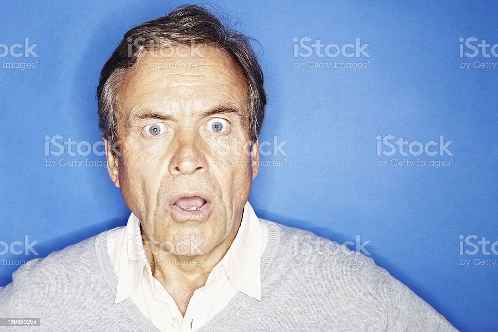 Closeup of a shocked senior man isolated against blue royalty-free stock photo
