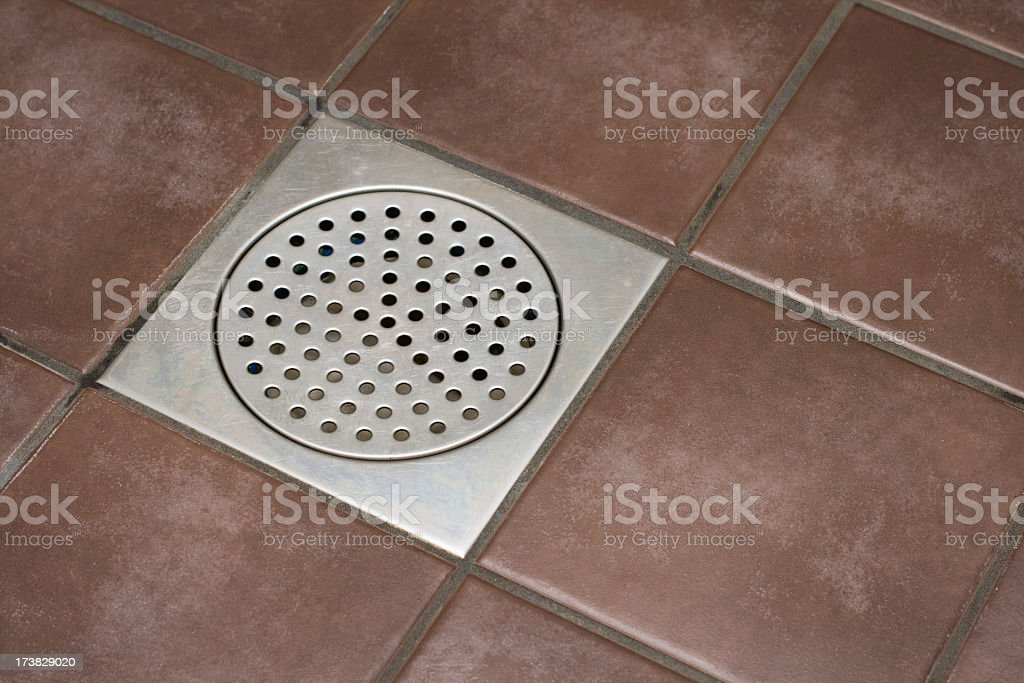 Close-up of a shower drain surrounded by brown tiles royalty-free stock photo