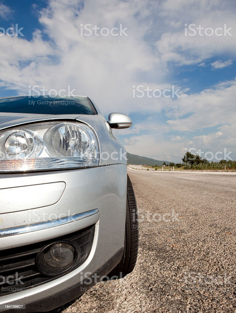 Close-up of a silver car's headlights on the road royalty-free stock photo