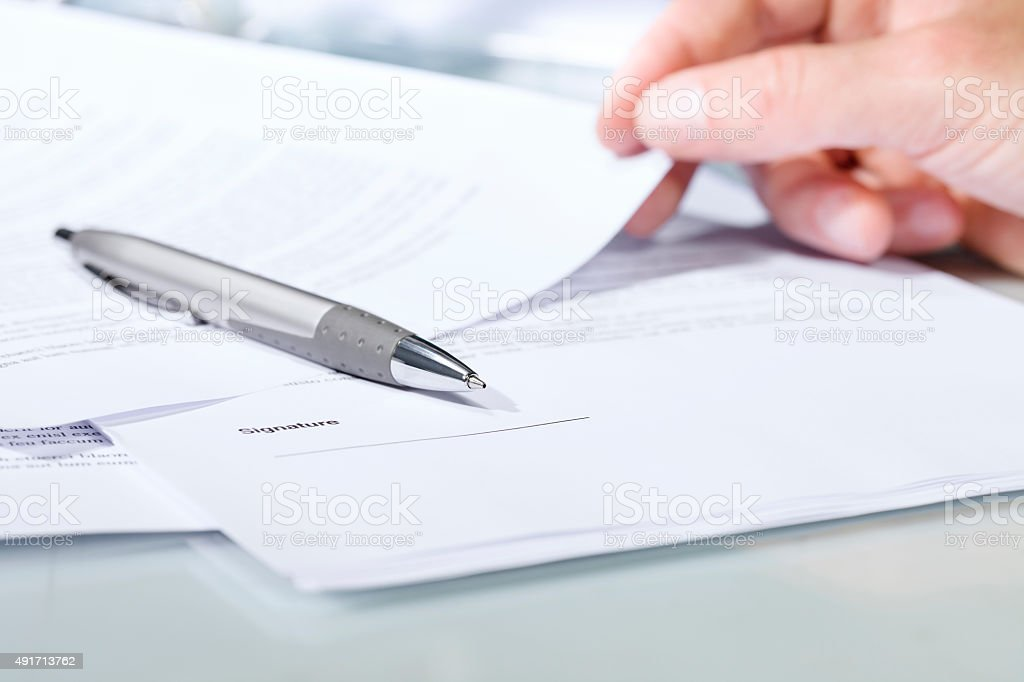 Close-up of a silver pen with documents. stock photo
