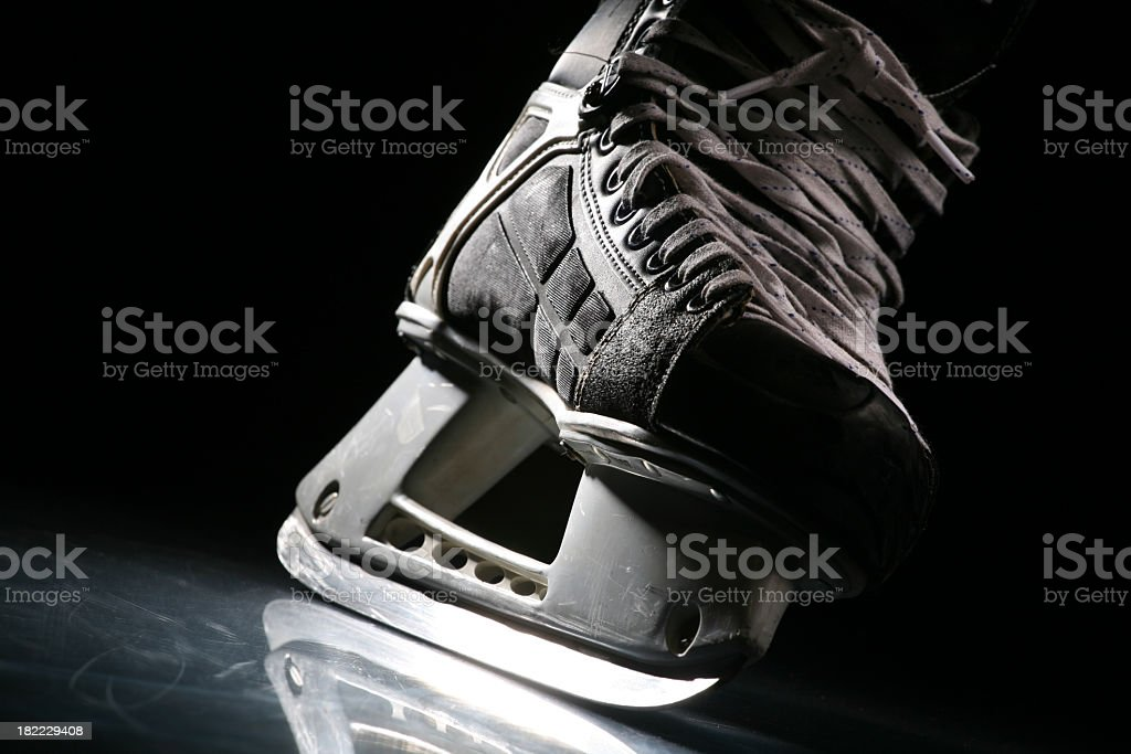 Close-up of a skate with sharp blade over shiny ice royalty-free stock photo