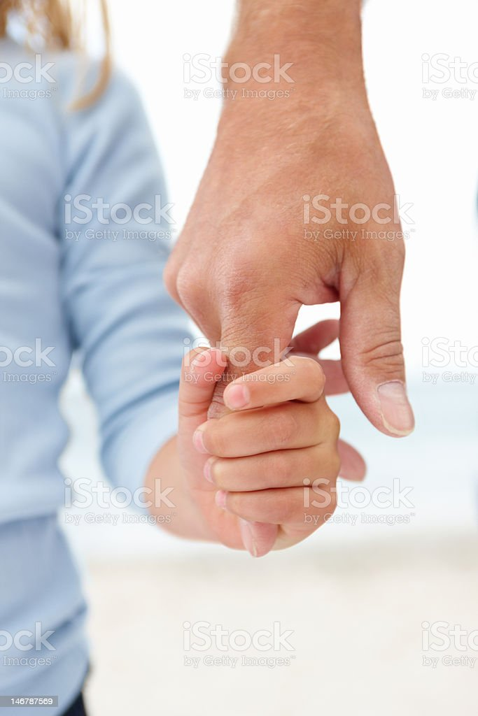 Close-up of a small girl holding an old man's finger stock photo
