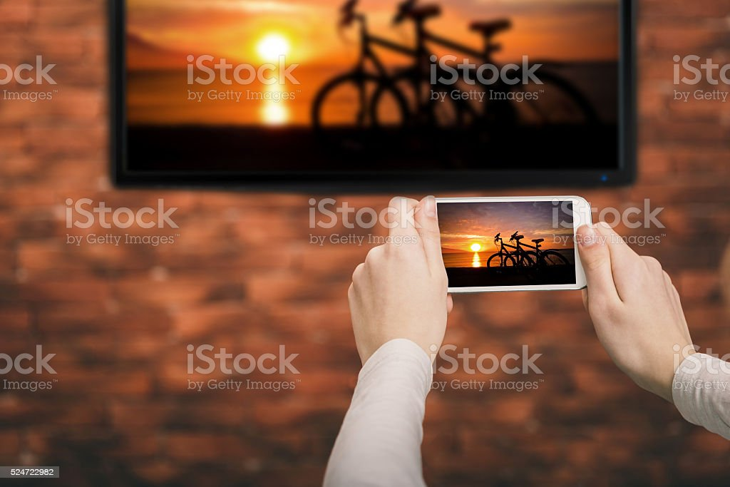 Closeup of a smart phone is connected to a smart TV. stock photo