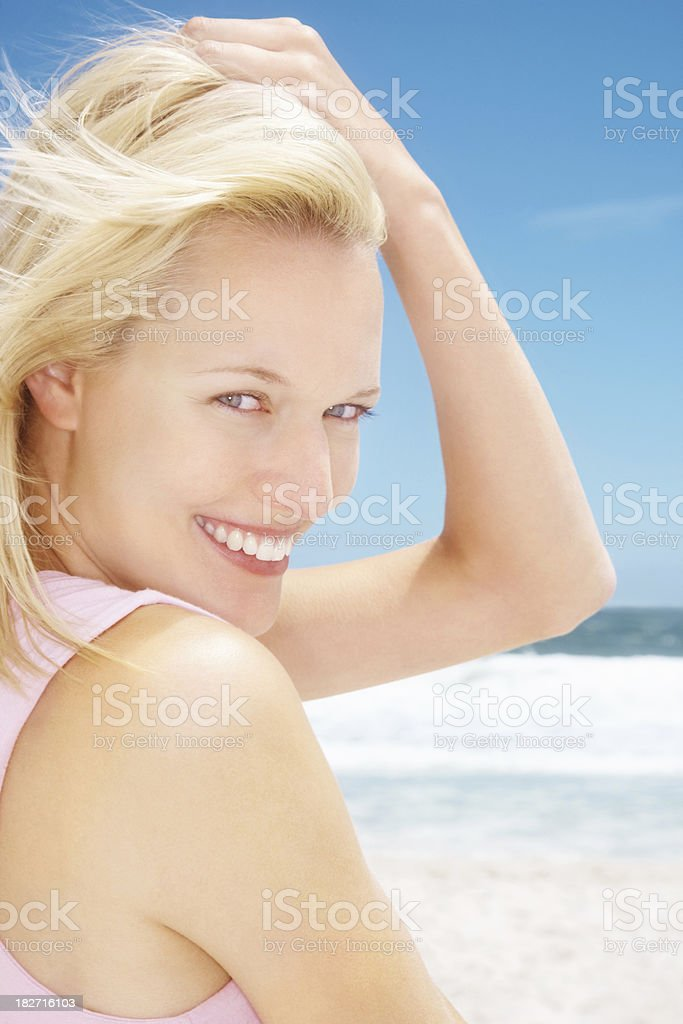 Closeup of a smiling blond female posing at the beach royalty-free stock photo