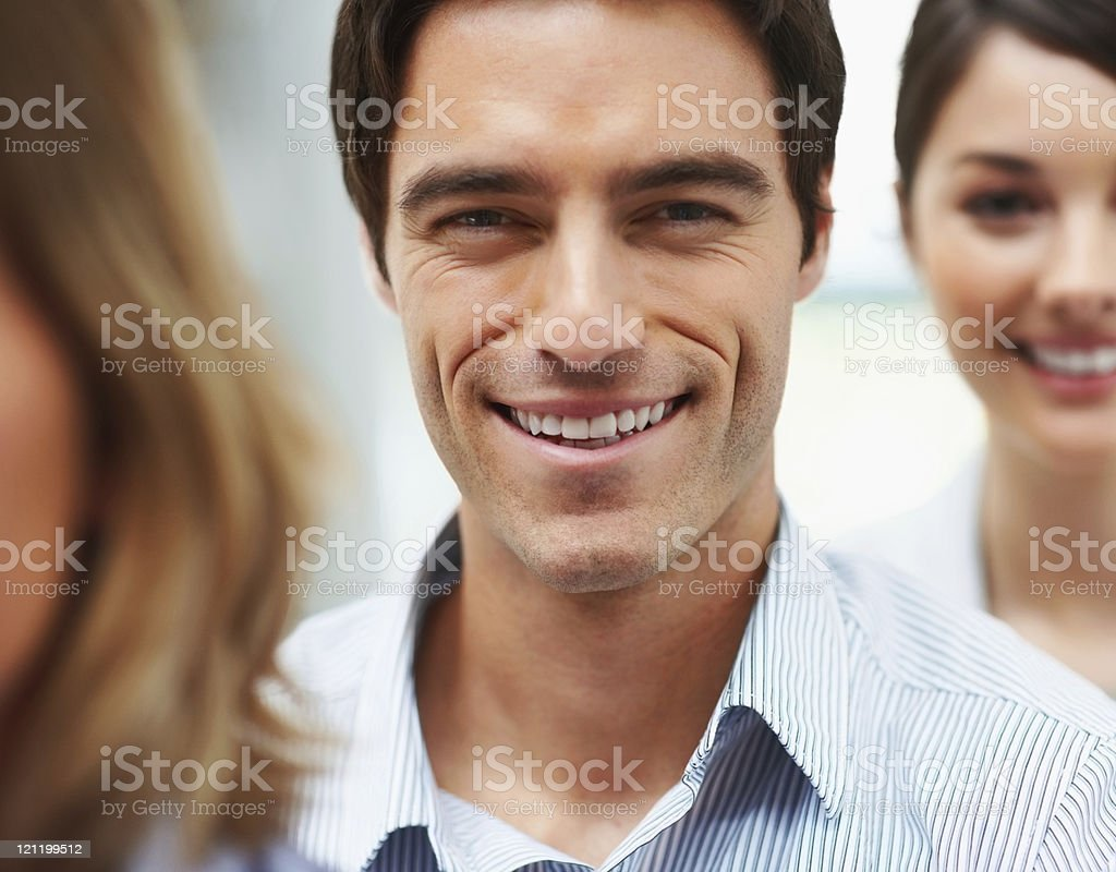 Closeup of a smiling business man in line with colleagues royalty-free stock photo