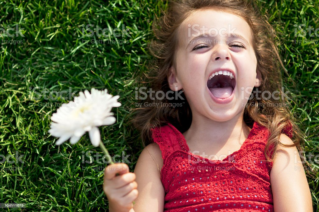 Close-up of a smiling little girl laying on the grass stock photo