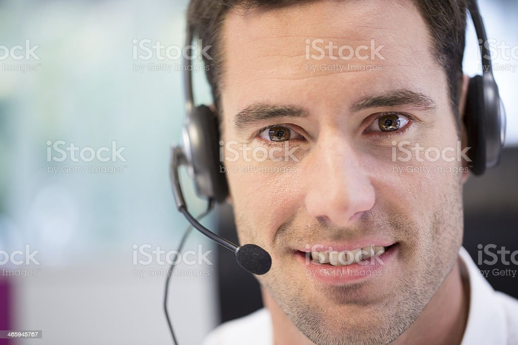 Close-up of a smiling man with a phone headset on stock photo