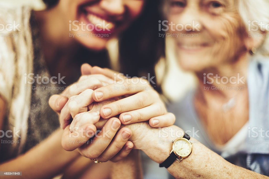 Close-up of a smiling nurse holding a senior woman's hand stock photo