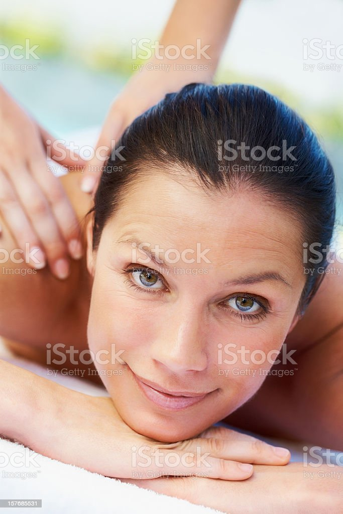 Closeup of a smiling woman getting shoulder massage royalty-free stock photo