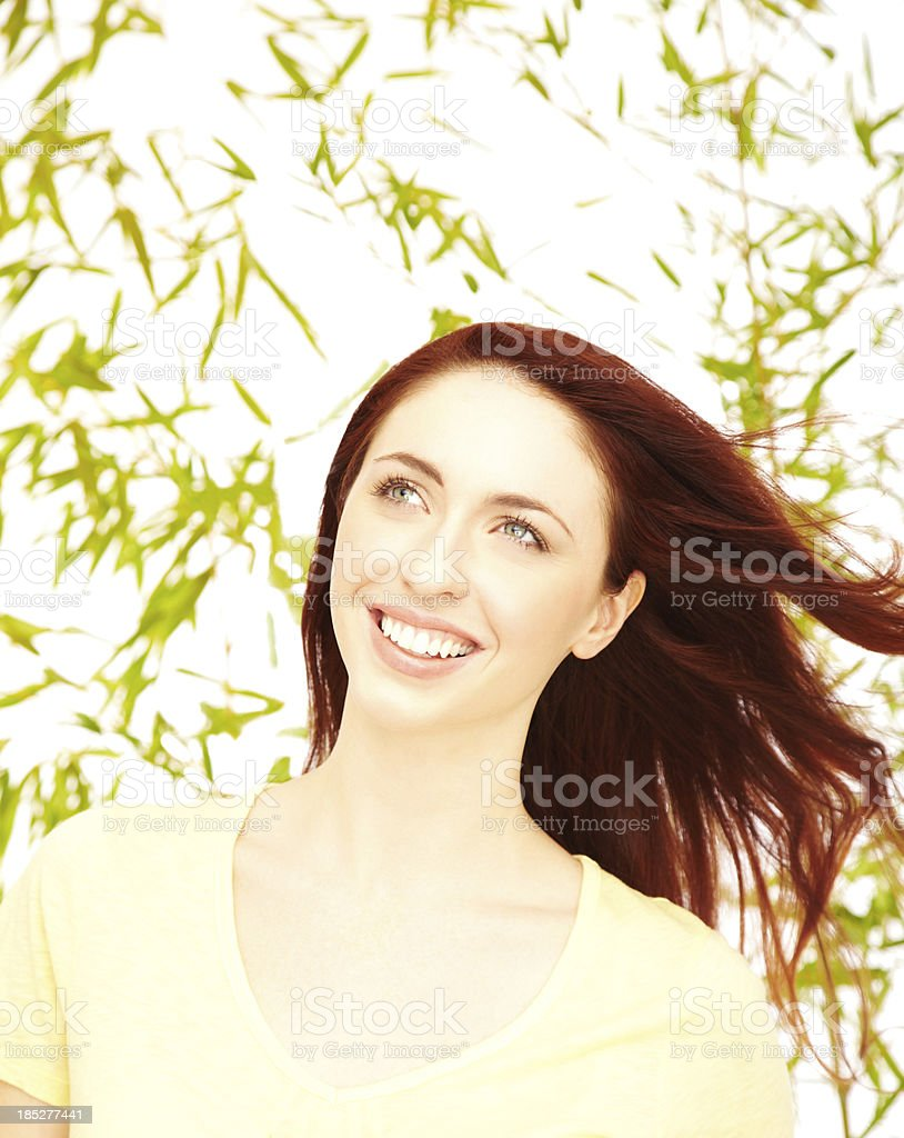 Close-up of a smiling young woman against nature background stock photo