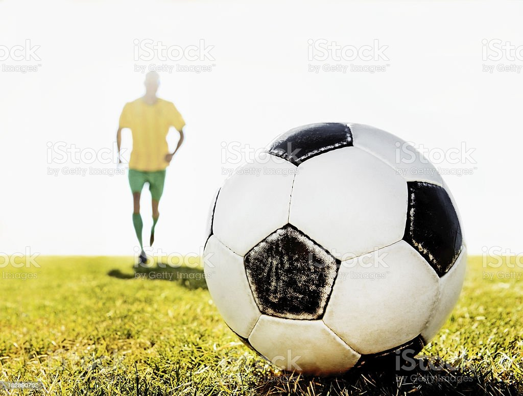 Closeup of a soccer ball with footballer in the background royalty-free stock photo