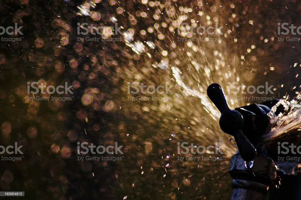 A close-up of a sprinkler head spraying water stock photo