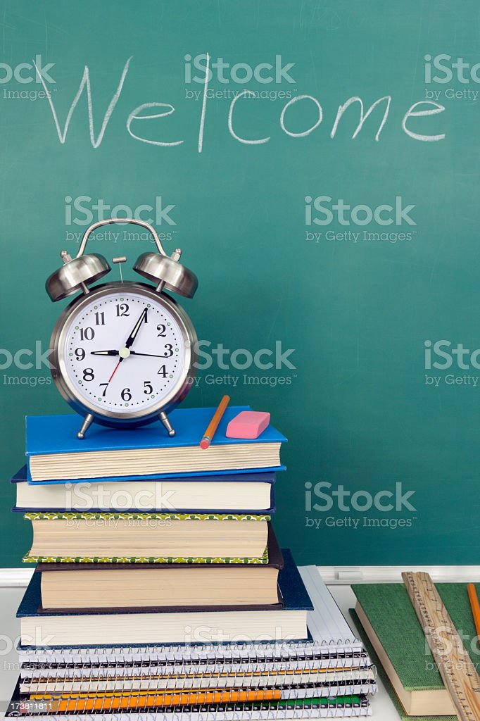 A close-up of a stack of books, clock, and a chalkboard royalty-free stock photo