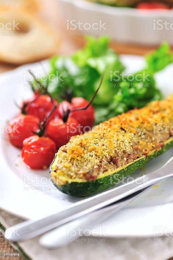 Closeup of a stuffed zucchini served with tomatoes and salad stock photo