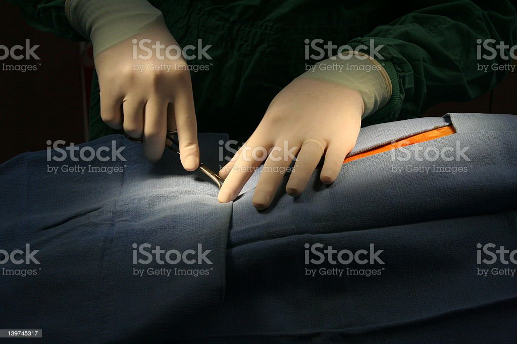 Close-up of a surgeons hands performing surgery stock photo