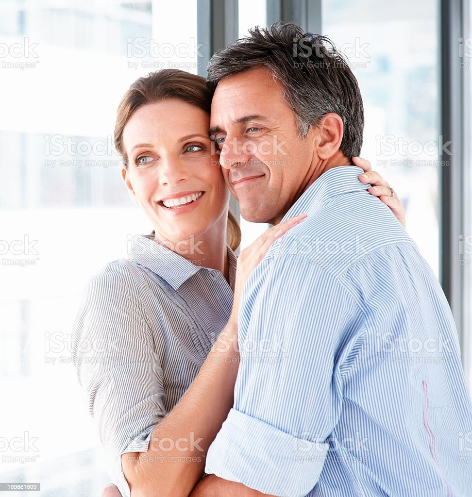 Closeup of a sweet couple embracing against white background stock photo