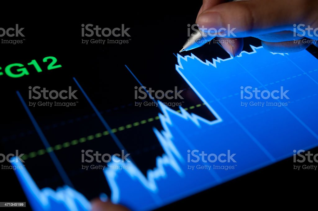 Close-up of a tablet with a market analysis graph in blue royalty-free stock photo