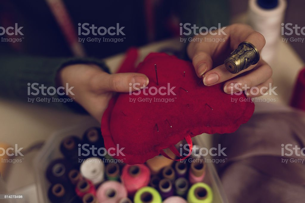 Close-up of a tailor holding heart shaped pin cushion. stock photo