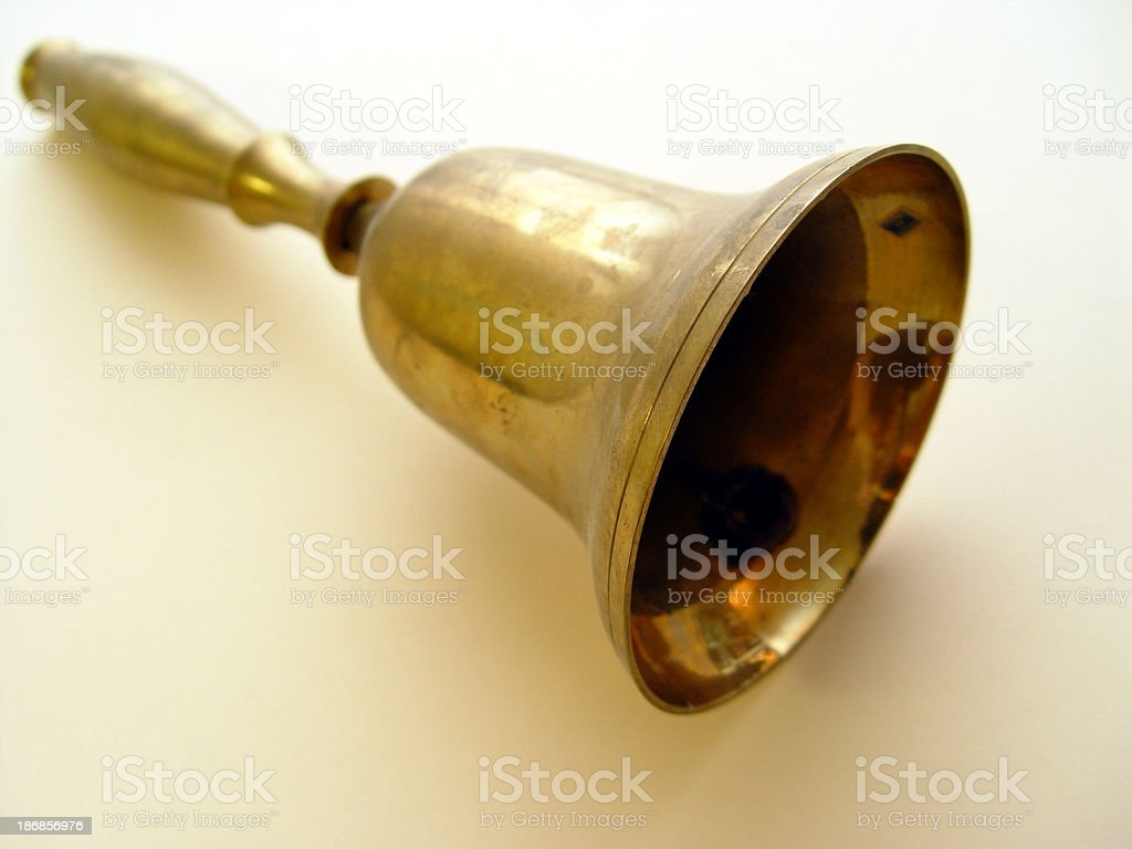 Close-up of a tarnished old gold colored bell lying down stock photo