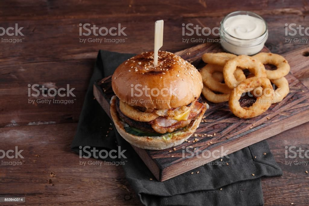 Closeup of a tasty Burger with appetizers such as fried onion rings with a white garlic sauce. Juicy Burger with bacon and cheese on a dark wood background stock photo