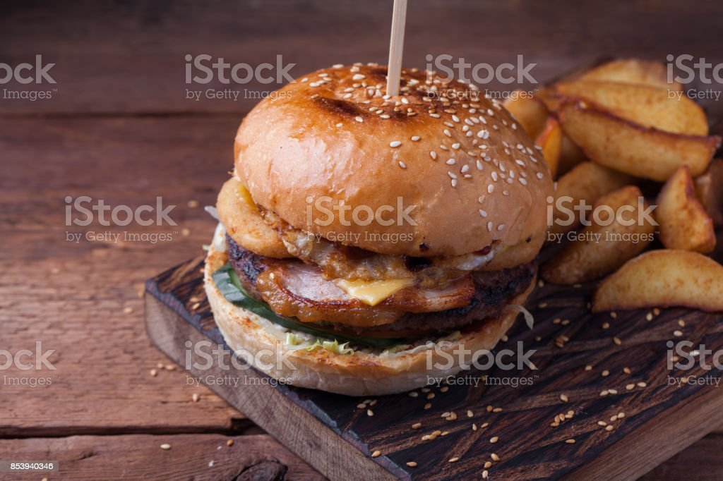 Closeup of a tasty Burger with snacks in the form of potatoes with white garlic sauce. Juicy Burger with onion rings, bacon and cheese on a dark wood background stock photo