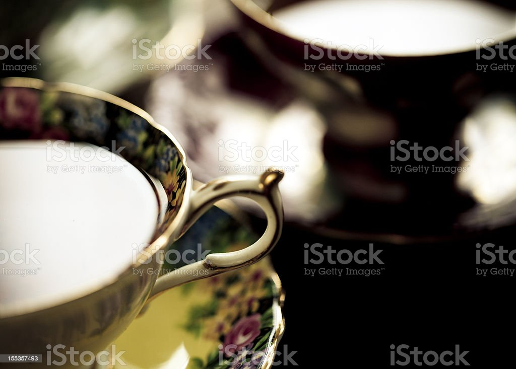 A closeup of a tea cup and saucer with gold trim stock photo