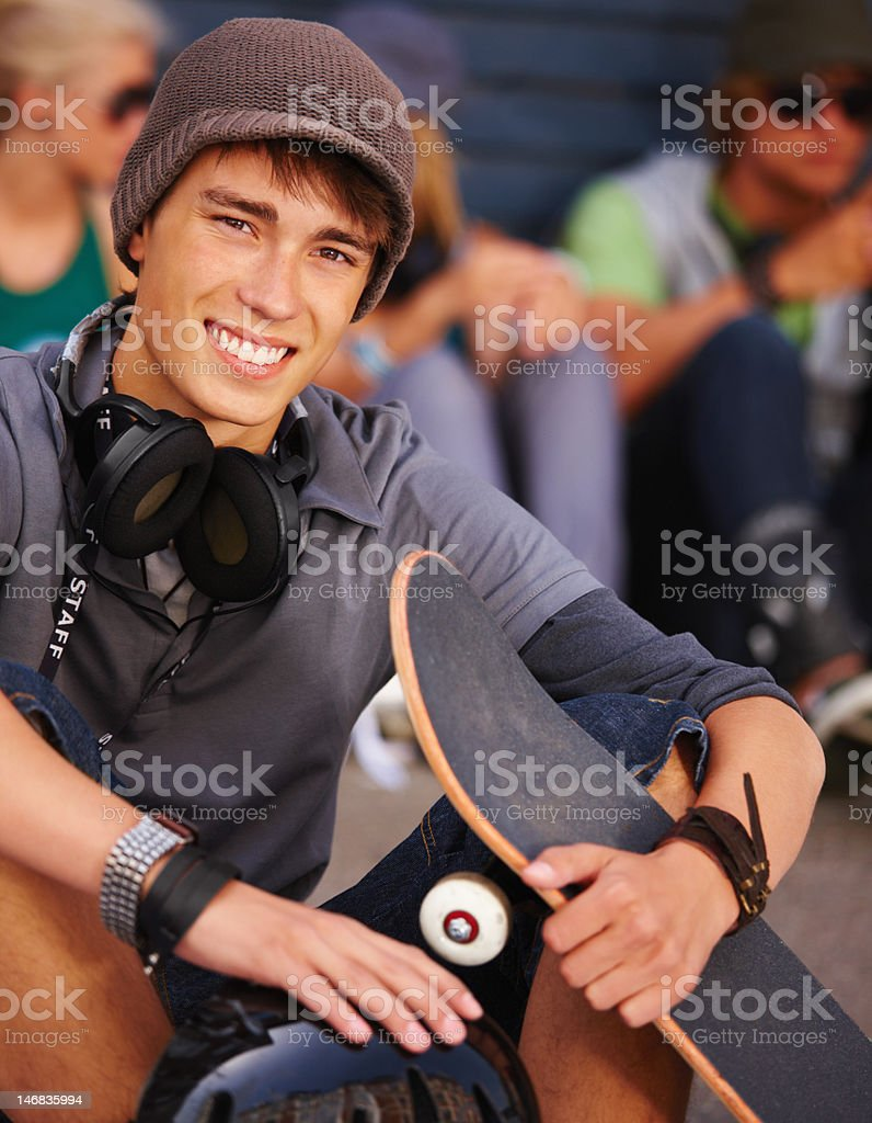 Close-up of a teenage boy sitting with skateboard and smiling royalty-free stock photo